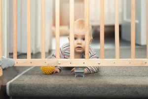 Baby,Playing,With,Ball,Behind,Safety,Gates